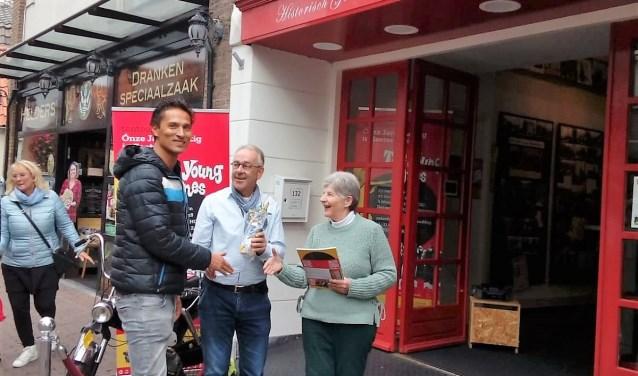 Tina Groen en Jacques Boonekamp hebben de 1000e bezoeker namens het HGOS een boek en een flesje aangeboden. Foto: pr