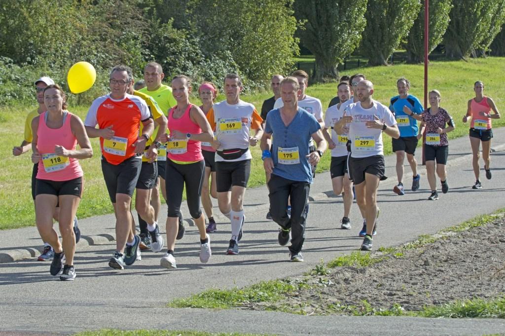 Deze hardlopers op de halve marathon richten zich op de 'pacer' (met ballon), een goede richtlijn om binnen een bepaalde tijd te lopen. Foto: stiefpaparazzi  © Postiljon