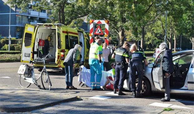De gewonde vrouw wordt verzorgd door ambulancepersoneel (foto: Lucien de Vries).
