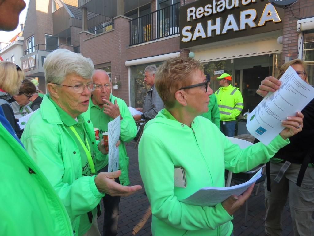 Deze vrijwilligsters in de Dorpsstraat hadden het zeer druk bij de inschrijving van de wandelaars. Foto: pr  © Postiljon