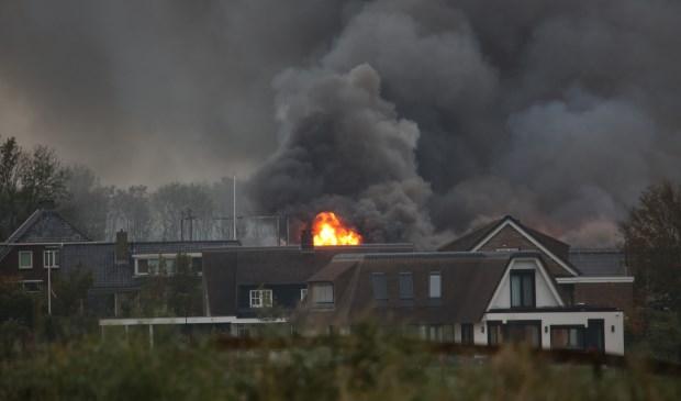 Een vuurzee en grote vlammen te zien achter de bebouwing in Stompwijk (foto: Roy Wolters/Regio15).