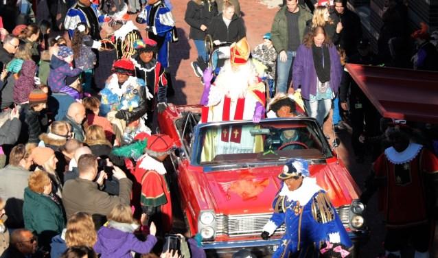 De aankomst van Sinterklaas in zijn 'bolide', een rode open Ford Galaxy 500, vergezeld door zijn pieten. Foto: Jan van Es