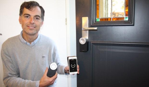 Ewout Hennipman laat zien hoe eenvoudig het is: een App op je telefoon en een apparaatje dat op je bestaande slot de cilinder in je slot naar links of naar rechts draait.