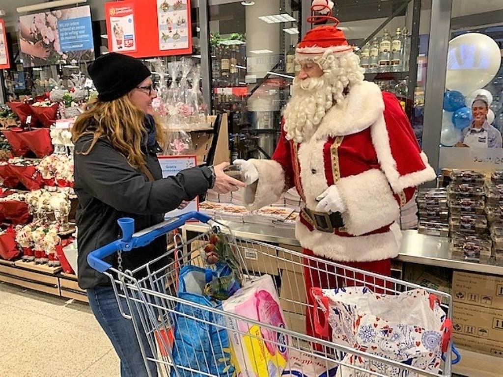 De Kerstman deelcadeautjes uit (foto: pr Hoogvliet).  © Het Krantje