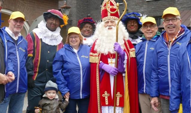 De Gastvrije Geuzen zijn herkenbaar aan gele petten en blauwe jacks. Hier zijn ze te zien met de Sint en enkele Pieten. Foto: Jan van Es