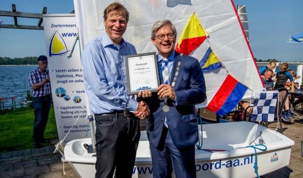 Burgemeester Aptroot reikt de oorkonde uit in verband met het 40-jarig bestaan van de watersportvereniging. Foto: Patricia Munster