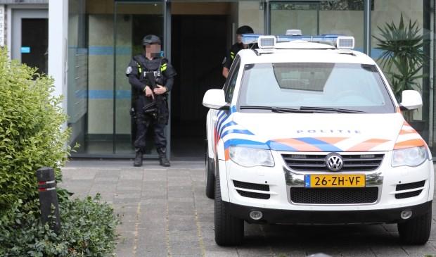 Twee ingangen van de flat werden bewaakt door zwaarbewapende politiemensen. (Foto: Regio15)