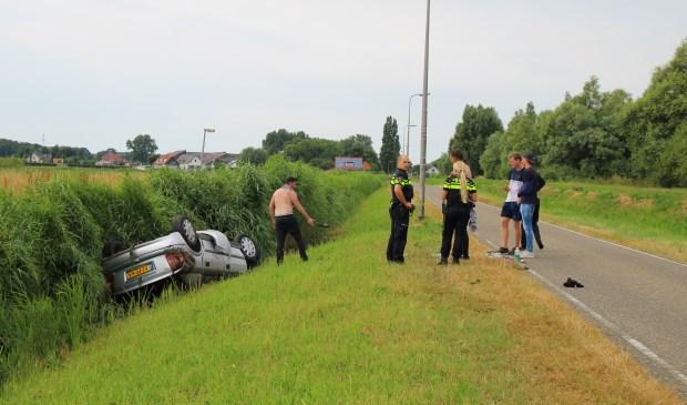De auto raakte door onbekende oorzaak in de sloot naast de weg (foto: Olav Spa).