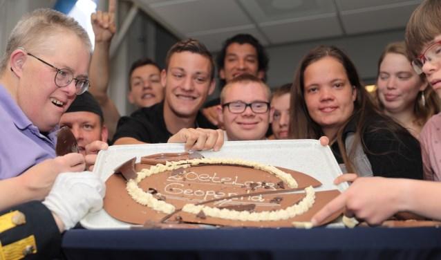 De cliënten konden niet wachten om een groot chocolade ei kapot te mogen slaan, waarin uiteindelijk een chocoladebord met de tekst 'Zoetelaar Geopend' zichtbaar werd. Foto: Jan van Es