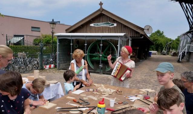 Angelique Schipper zingt liedjes bij De Salamander, terwijl kinderen figuurzagen (foto: Ot Douwes).