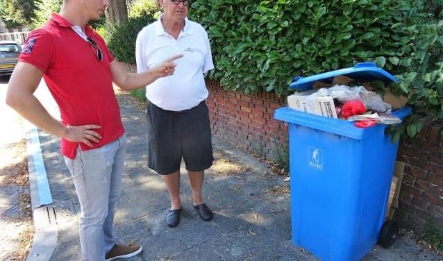 Raadslid Gijs Dupont en een omwonende inspecteren de overvolle blauwe containers die er al lange tijd staat (foto: Ap de Heus).
