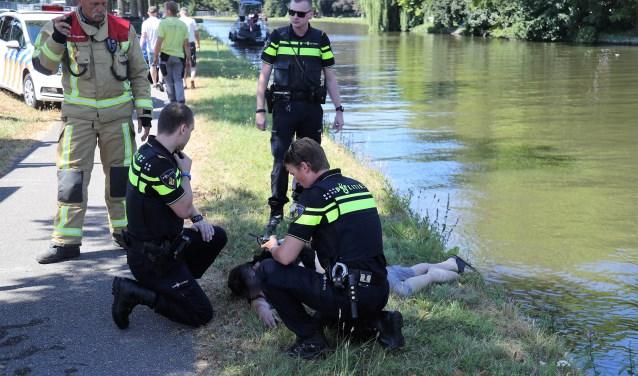 Het slachtoffer ligt bij te komen nadat hij op de kant is geholpen (foto: Rene Hendriks/Regio15).