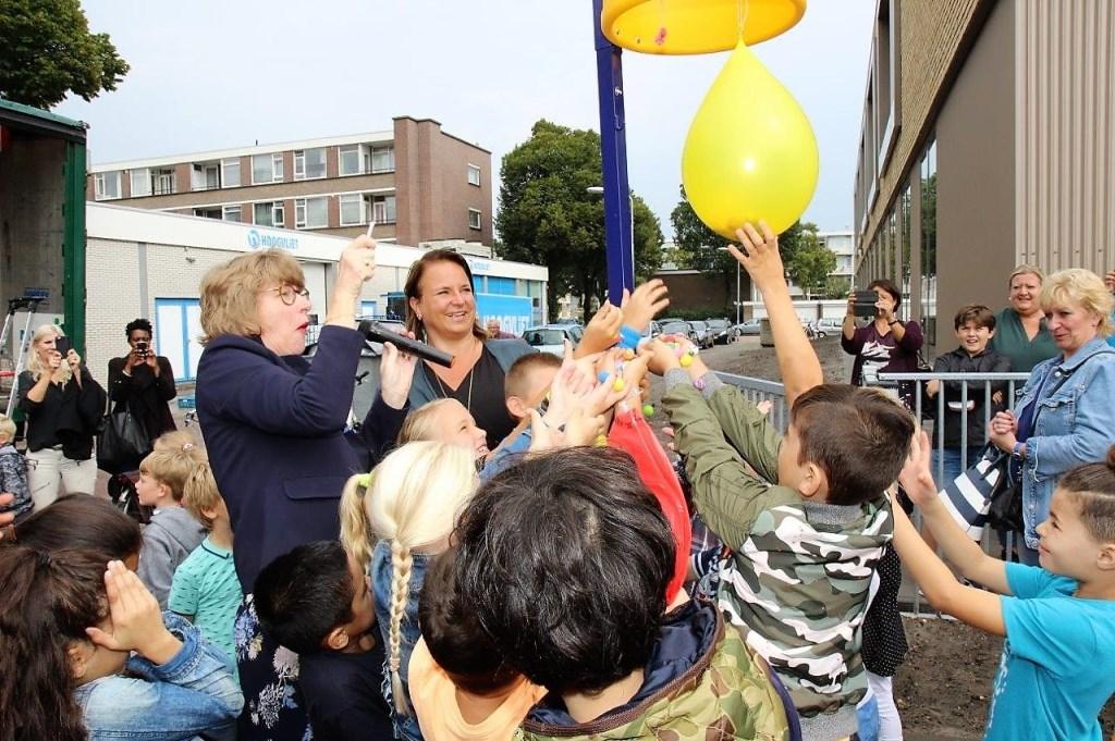 De wethouders prikken een ballon met knikkers door, die door de kinderen mochten worden opgeraapt (foto's: Ap de Heus).
