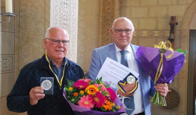 Theo van der Hoeven (l.) en Fons van der Linden (r.) ontvingen de Nicolaaspenning voor vele jaren vrijwilligerswerk in de H.Nicolaasparochie. Foto: pr