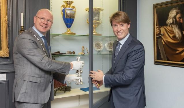 Burgemeester Klaas Tigelaar plaatst samen met Wibo Schepel de bokaal in de vitrine (foto: Michel Groen).