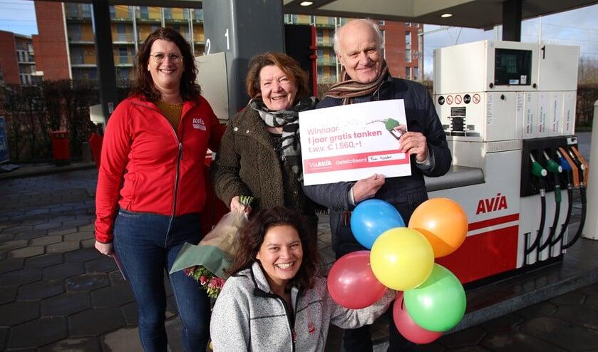 Marga en Rob Koster mogen een jaar gratis tanken bij AVIA. Ze kregen een cheque en bloemen van Cindy en Ruby van AVIA Pijnacker.