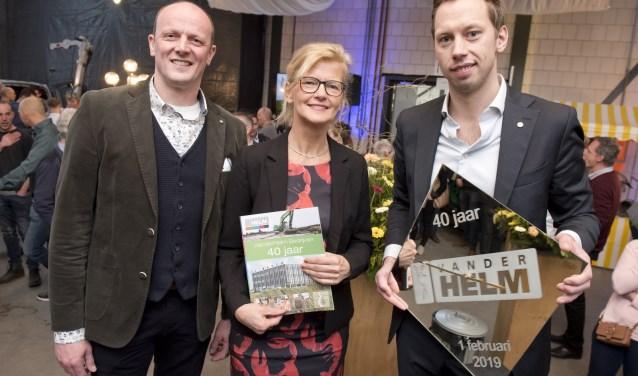 Gijs van der Helm (met een cadeau van de medewerkers) en Anton Dijkshoorn overhandigden het eerste exemplaar van het jubileummagazine aan Marja van der Helm. (Foto: Cok van den Berg)