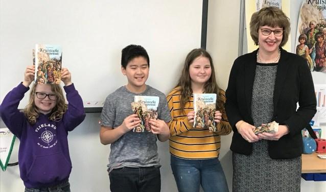 Wethouder Juliette Bouw overhandigde het eerste exemplaar van het jeugdboek 'Kruistocht in spijkerbroek' aan leerlingen van basisschool De Parachute (foto: gemeente LDVB).
