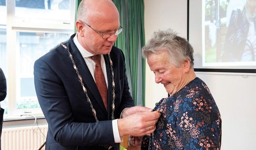 Burgemeester Klaas Tigelaar speldde Mw. Went-Rurup de versierselen op, behorende bij haar benoeming tot Lid in de Orde van Oranje-Nassau (foto: Michel Groen).