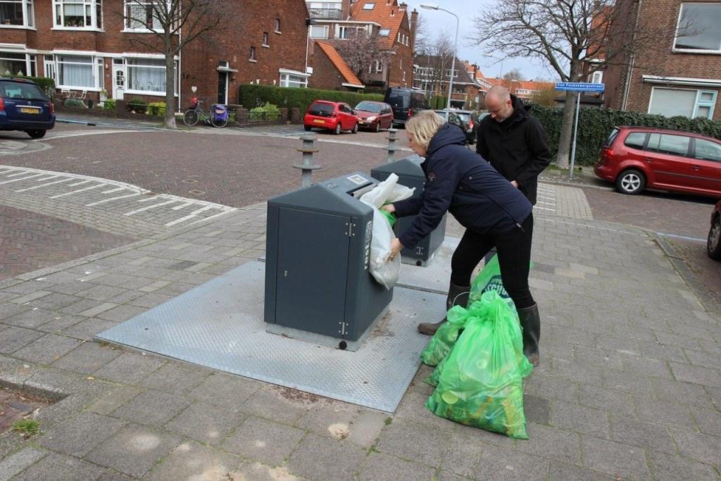 Wethouder Van Eekelen propt de zakken met zwerfafval in de container (foto: Ap de Heus).  © Het Krantje