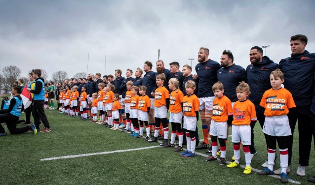 De jeugdleden als player escorts bij de rugbyspelers van het Nederlandse en het Portugese rugyteam (foto: pr VRC).