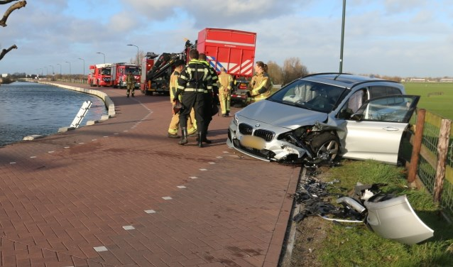De schade aan zowel het voertuig op de kant als de auto in het water is groot (foto: Ruben van Essen).