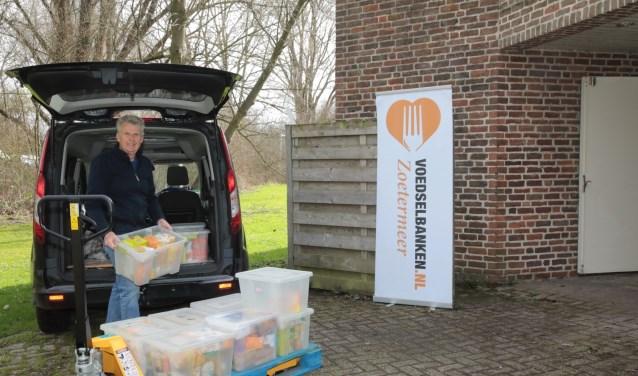 Ruud Mons, coördinator van de Voedselbank Zoetermeer is bezig goederen uit zijn bestelwagen te halen. Foto: Jan van Es