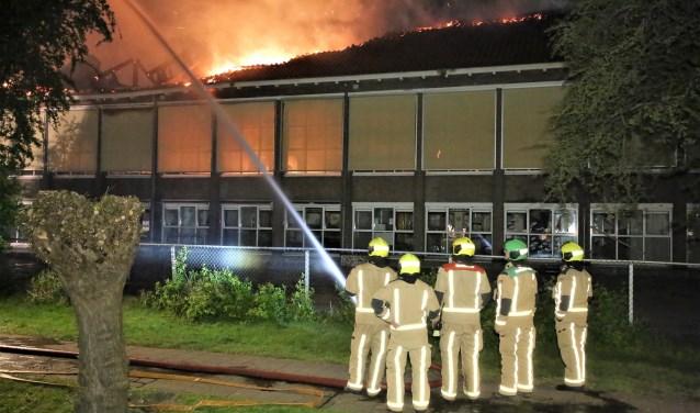Het vuur sloeg al snel door het dak van de Maerten van de Veldeschool, waarna het te gevaarlijk werd om het pand te betreden en de school als verloren werd beschouwd (foto: Regio15).