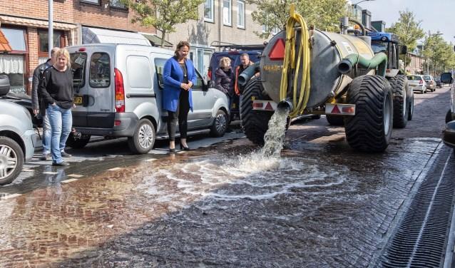 Door het legen van een watertank werd een regenbui nagebootst. Wethouder Stemerdink hield het nog net droog (foto: Michel Groen).