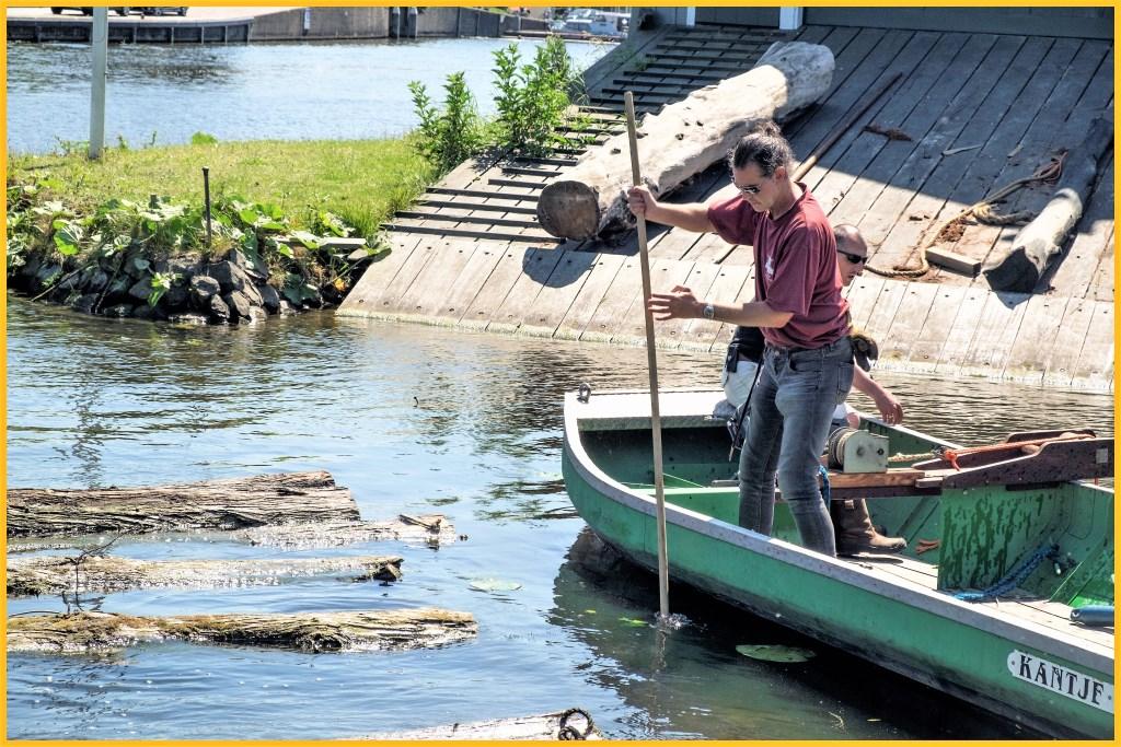 Aan het werk met boomstammen in het balkengat bij de molen. E. Brinkman © Het Krantje