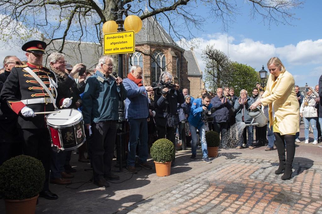 Wethouder Astrid van Eekelen opent het mozaiek in de Herenstraat door het met een gieter te bewateren (foto: Michel Groen). Michel Groen © Het Krantje