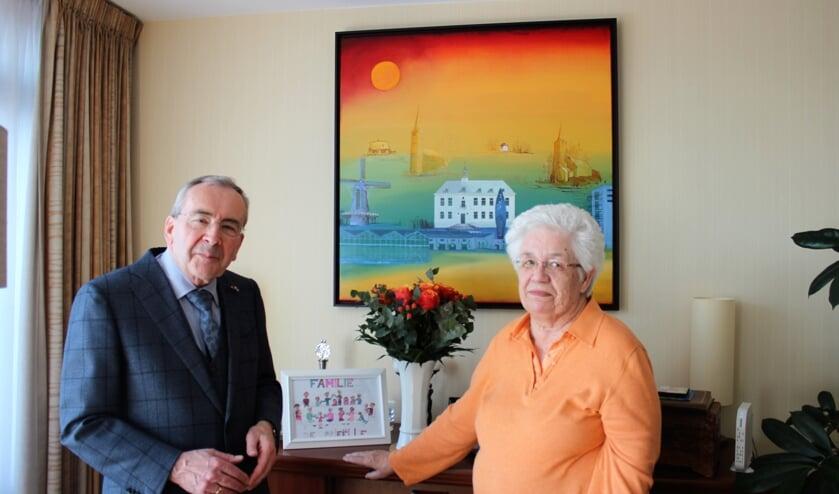 John de Prieëlle met zijn vrouw Thera bij het schilderij van Ries Kleijnen. Dit kreeg hij bij zijn afscheid als burgemeester van Pijnacker. Op het dressoir staat een familietekening gemaakt door een van de kleinkinderen.