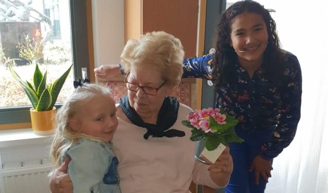 Jade (6 jaar) en Nasira (11 jaar) brengen voorjaarsplantjes naar ouderen in woonzorgcentrum Vivaldi Zoetermeer. Foto: pr