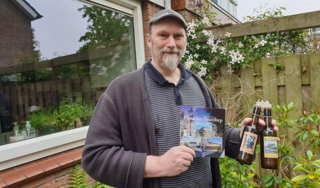 Erik met bier en boeken in de groene achtertuin van zijn vriendin.