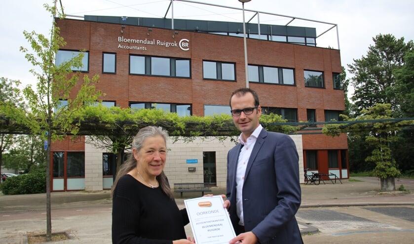 Heily van der Jagt overhandigt de Fair Trade-oorkonde aan directielid Danny Ruigrok.