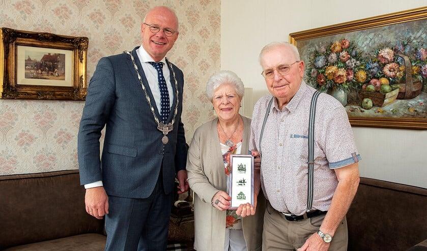 De heer en mevrouw Officier-Prins met burgemeester Klaas Tigelaar en de ets met afbeeldingen van drie lokale historische panden in Leidschendam-Voorburg (foto: Michel Groen).
