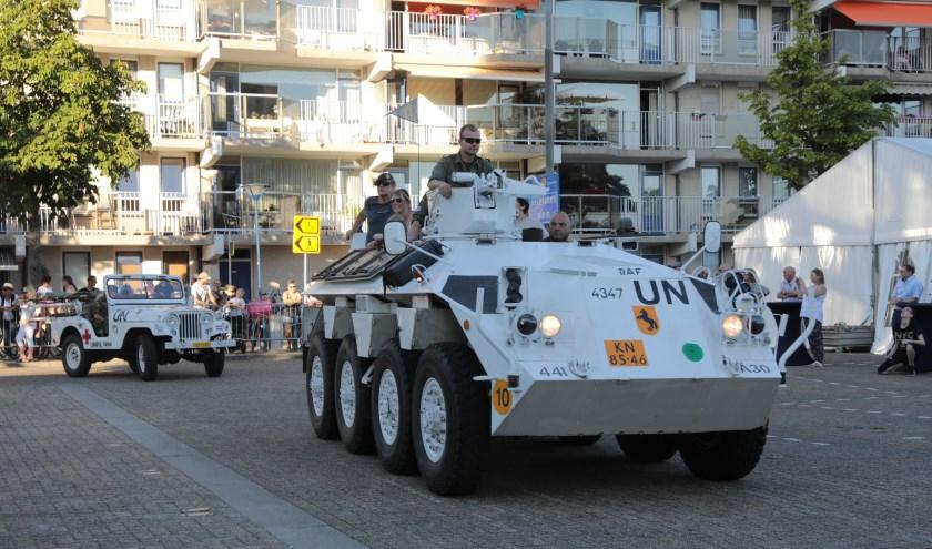 Een Nederlandse pantserwagen met daarachter een jeep, beide in VN kleuren, rijden de Markt op. Foto: Jan van Es