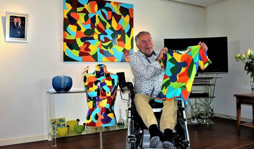 Gerard de Gier met een T-shirt met zijn kleurenpatroon, achter zich een schilderij en naast zich een beschilderde torso (foto/tekst: Dick Janssen).