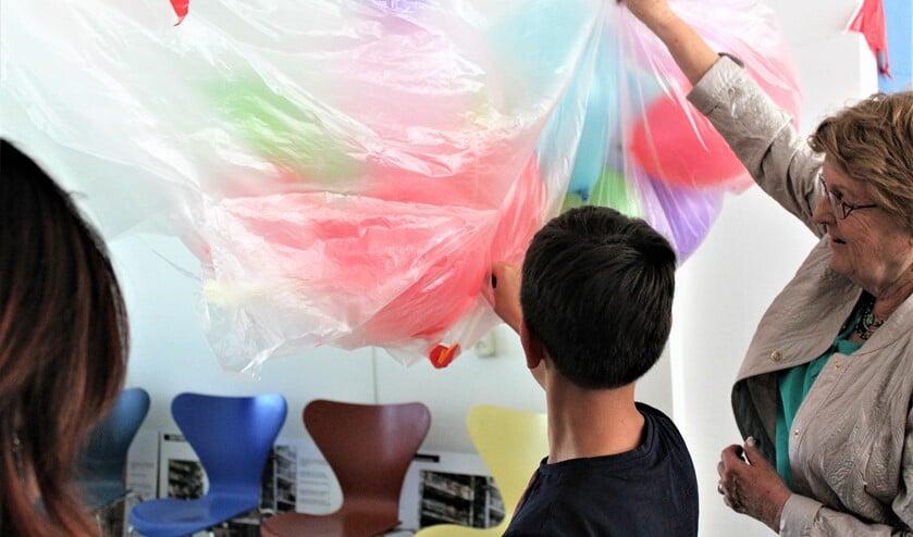 Met het doorprikken van vele ballonnen verrichtte mevrouw Eijckelhof met een jonge bewoner, de openingshandeling (foto: pr).