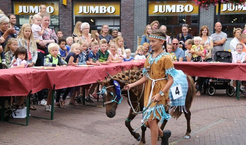 De tienjarige Juliet, verkleed als indiaan, won de ponybrunch. Ze maakt een ererondje over het plein. (Foto: Sander de Hollander)