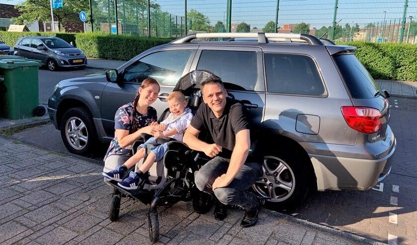 Sjors met papa en mama bij de auto die eigenlijk te klein is om zijn elektrische rolstoel in te kunnen vervoeren (familiefoto).