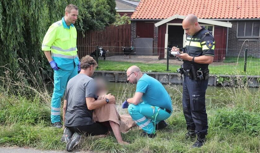 De passant en ambulancemedewerkers ontfermen zich over de man, terwijl de politie gegevens noteert (foto:Rene Hendriks).