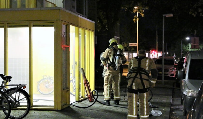 Brandweerlieden actief bij een van de portieken die vol rook hingen (foto: Herman van der Woude).