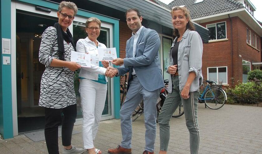 v.l.n.r. Nienke Oldenhuis en Francis Bennis bieden vol trots de informatieve folder over Mantelzorg aan huisarts Sander Gransjean en praktijkondersteuner Lilian Maas aan.
