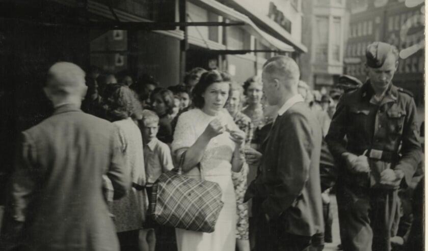 <p>IJsjes eten bij &nbsp;Florencia, rechts loopt een Duitse soldaat voorbij, 1943. Foto: Collectie Haags Gemeentearchief</p>