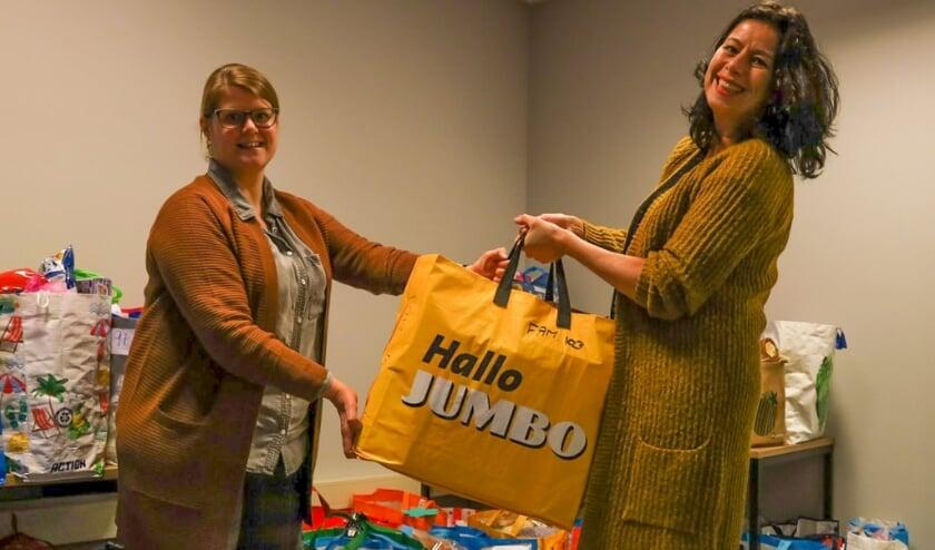 <p>In het kader van de actie Omgekeerde Adventkalender levert Petra Sevinga, stadsdeeldirecteur Leidschenveen Ypenburg haar kerstpakket in bij Marjolijn Vreeken (HECHT Leidschenveen Ypenburg). Foto: pr</p>