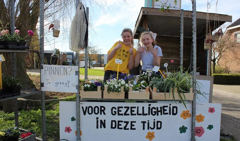 """Ook Zorgkwekerij Bloei aan de Europalaan in Pijnacker blijft positief. Evie de Hoog en Julia Ammerlaan verkopen bloemige bakjes """"gezelligheid"""". (foto: Martijn Mastenbroek)"""