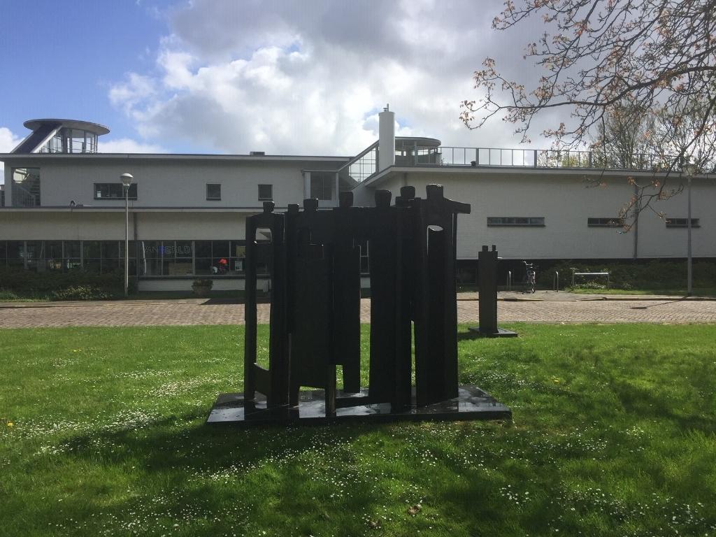 De sculptuur van zes personen op het ILSY-plantsoen, met op de achtergrond het gerestaureerde stationsgebouw van voormalig vliegveld Ypenburg. Foto: Peter Zoetmulder  © Telstar Uitgeverij B.V