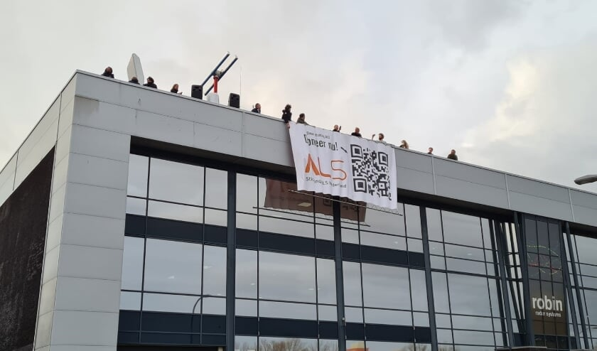 <p>Het moment van tijdelijk uitrollen op donderdag. De banner is vanwege het stormachtige weer weggehaald, maar gaat deze week met een hoogwerker omhoog. Foto: pr&nbsp;</p>