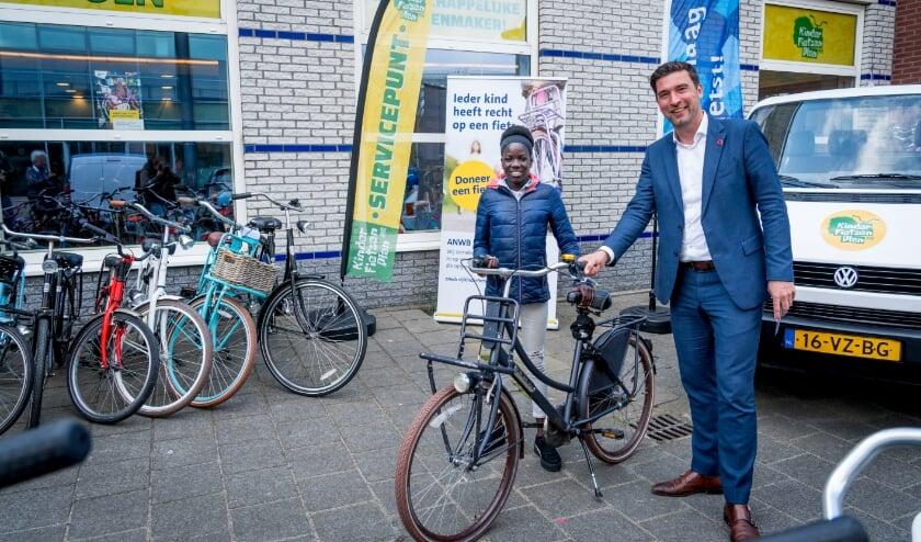 <p>Wethouder Robert van Asten geeft de eerste Haagse fiets uit dit plan aan Laura. Foto: Valerie Kuypers<br><br></p>